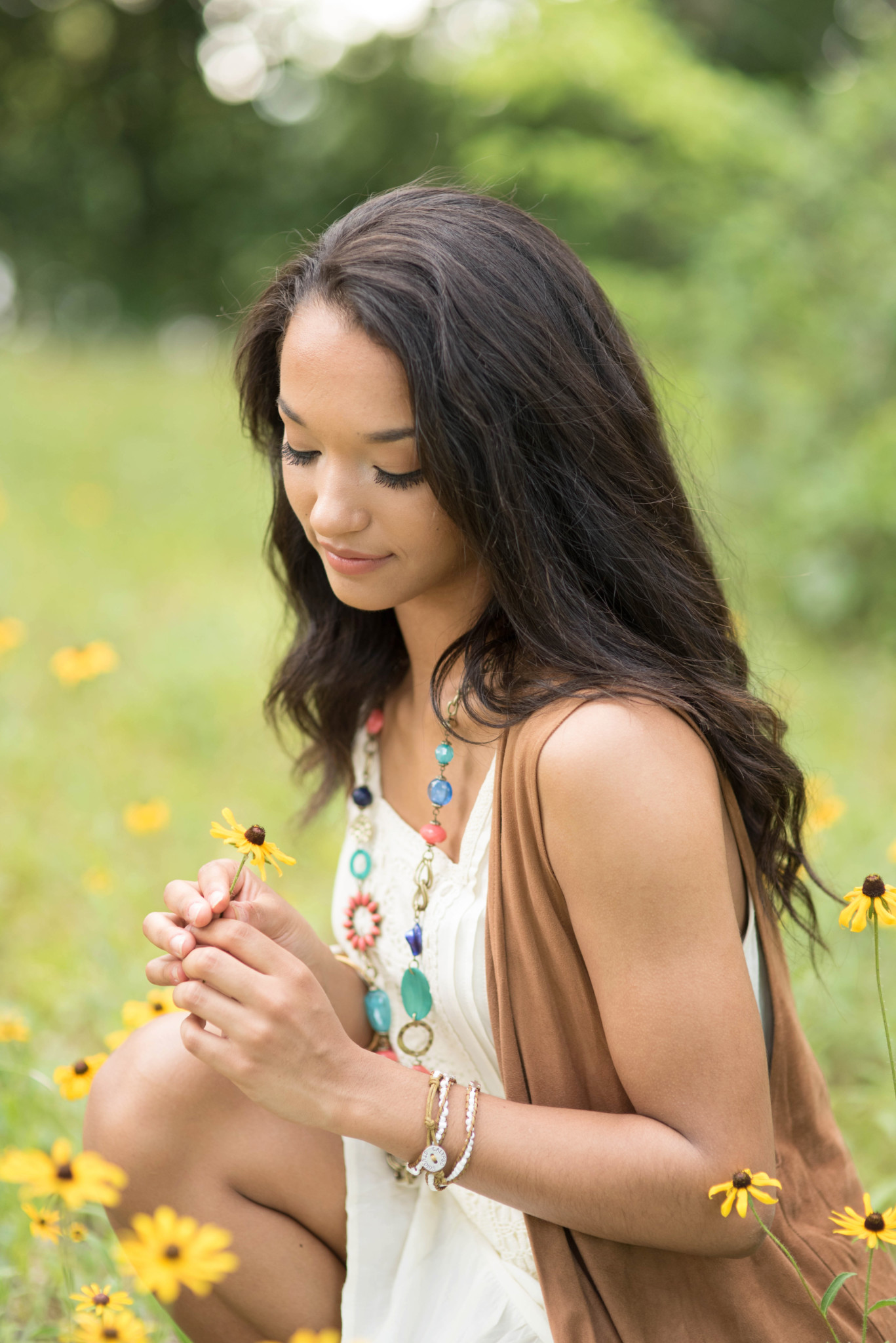 north allegheny high school senior kneels in field of yellow flowers during her senior pictures in wexford pa