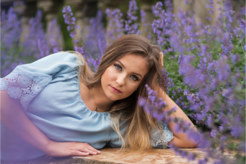 north allegheny high school senior lays in field of purple flowers during her senior picture session with wexford pa photographer