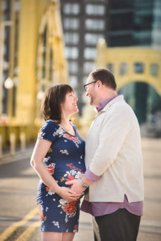 Pregnant couple are in Downtown Pittsburgh for Maternity Photos on the Clemente Bridge
