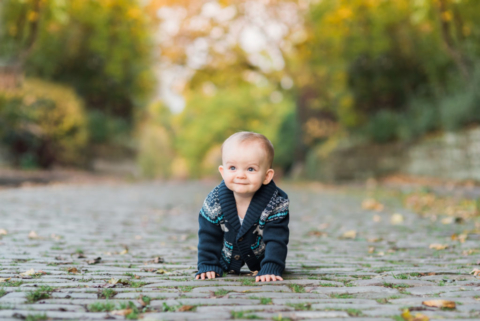One year old boy smiles as he crawls on a cobblestone street. He wears a navy sweater and green and yellow trees shine in the background for this Pittsburgh family photographer session