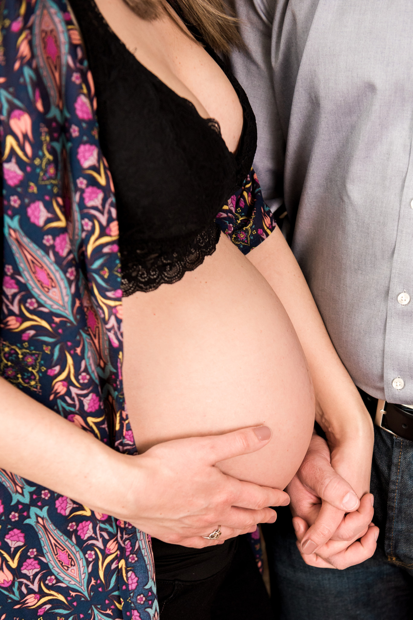 Expectant Pregnant mom wearing a black bra and floral robe holds hands with her husband as she caresses her stomach