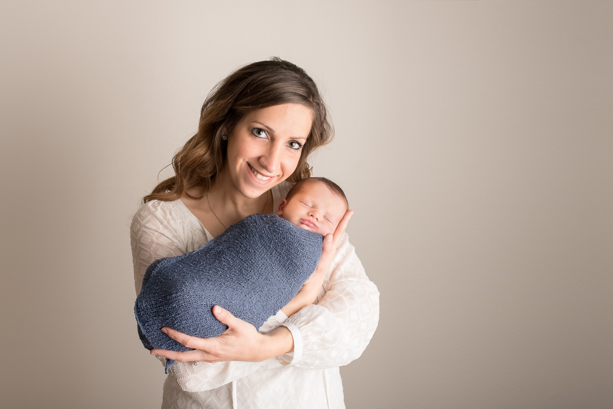 A mother proudly holds her son while wrapped in a blue swaddle during their newborn portrait photography session in Pittsburgh, PA