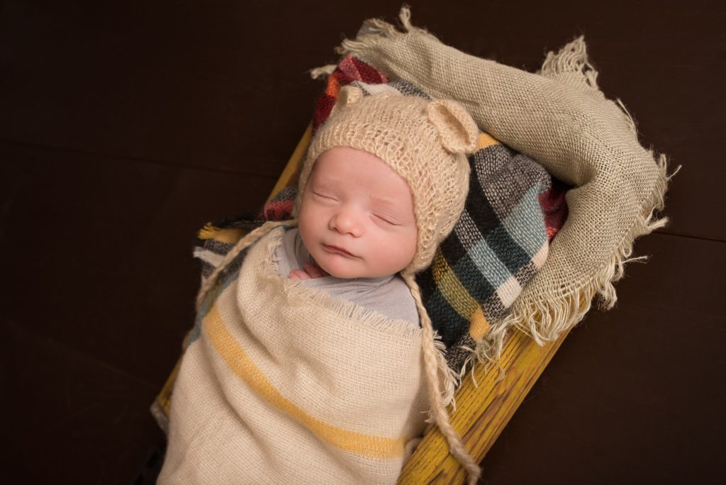 A baby boy wrapped in a fall burlap and plaid blanket wearing a knit hat during a newborn portrait photography session in Cranberry Twp Pittsburgh PA
