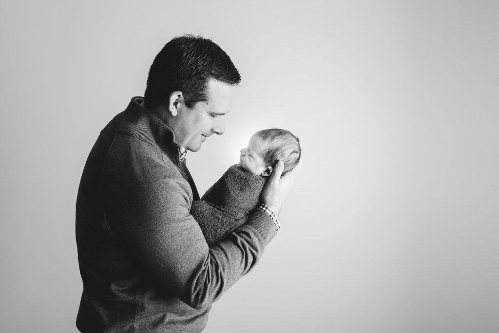 A father looks at his son while wrapped in a swaddle during a photography session in Sewickley, PA