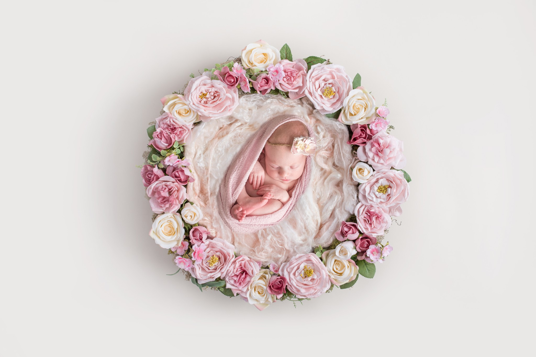 A newborn baby girl lays upon layers of pink fabric while laid in a basket adorned with florals/flowers during her newborn portrait photography session in Wexford PA near Pittsburgh