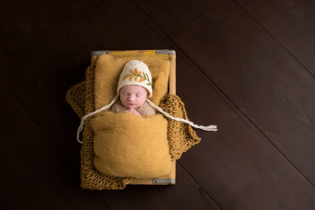 A baby girl rests in mustard gold fabrics and knits in a vintage crate with a goldenrod bonnet during her Pittsburgh newborn photography session in Cranberry Twp PA