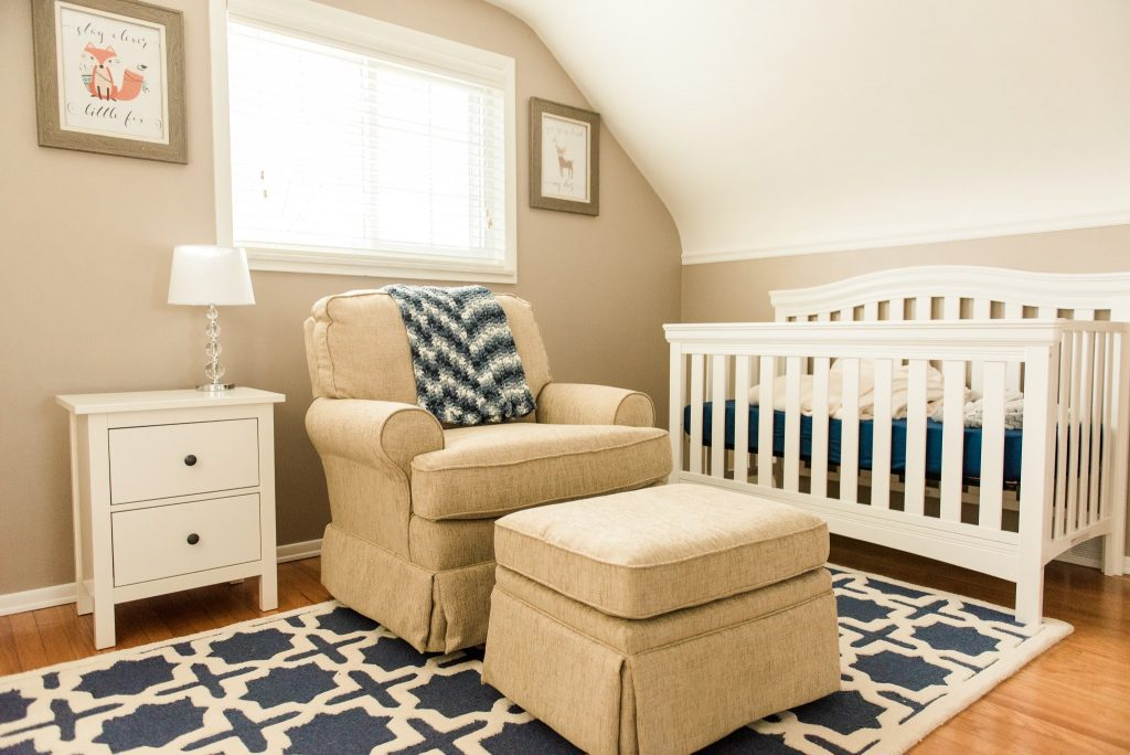 A neutral baby nursery with a white crib and blue accessories in a Pittsburgh home.