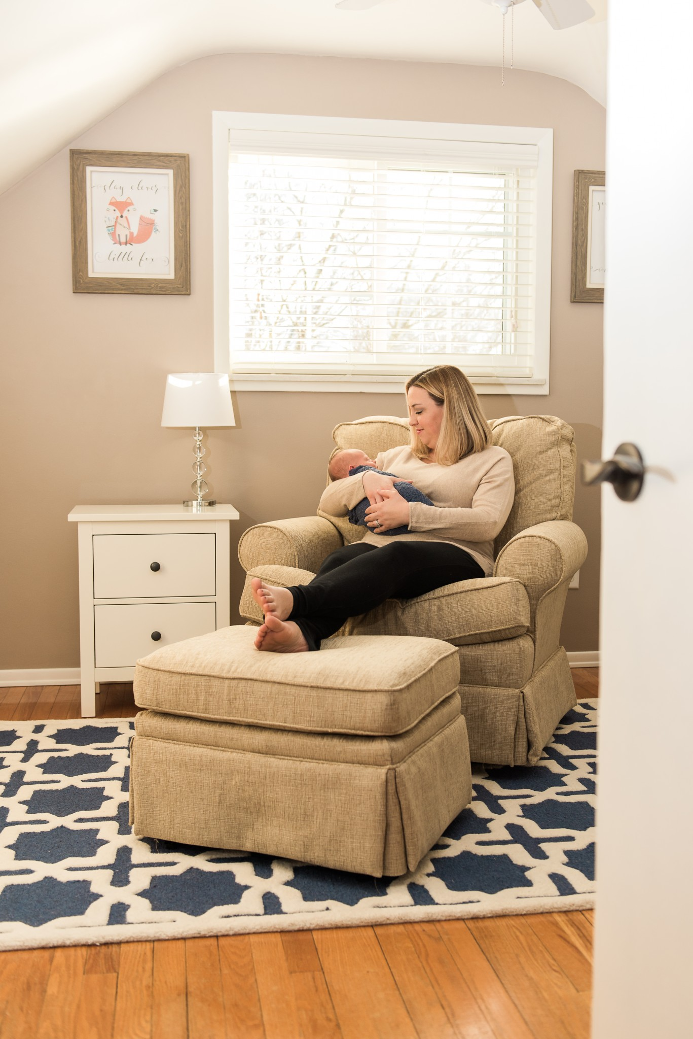 A baby boy is held in a blue swaddle while mom is seated in a neutral tan, white, and blue nursery in their Pittsburgh home.