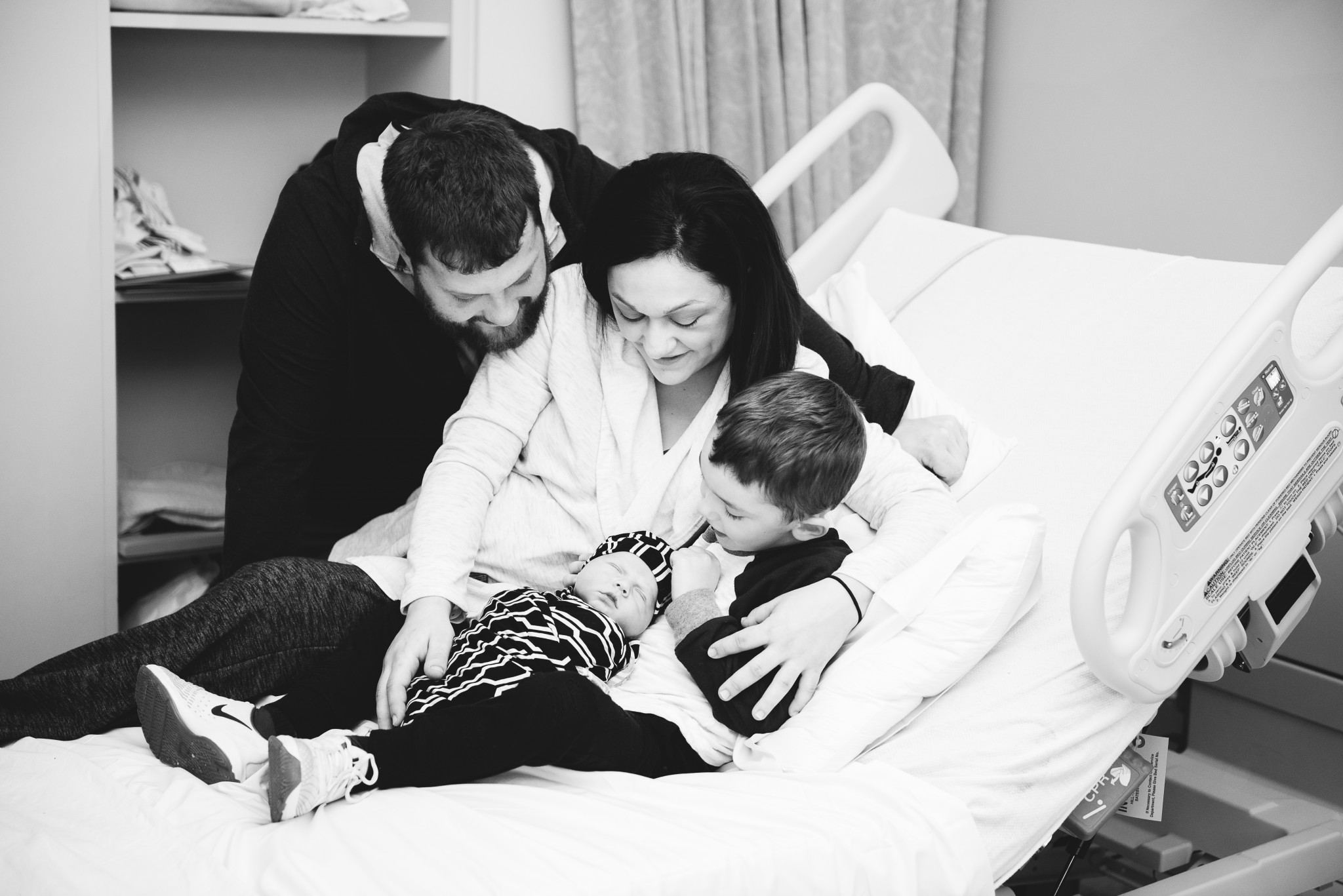 A new family of four gather on the hospital bed during their photography session in a Pittsburgh hospital.