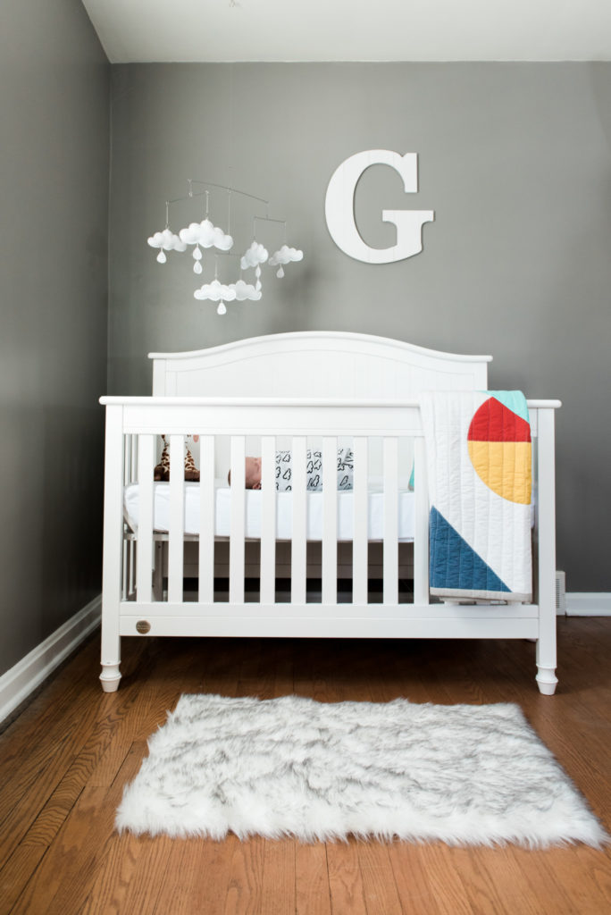 Baby boy wrapped in a white swaddle lays sleeping in his white crib. Above the crib on the wall is a large letter G and a cloud mobile. On the floor lays a white fur rug and on the crib hangs a colorful quilt for this in home newborn lifestyle photography session in Pittsburgh, PA