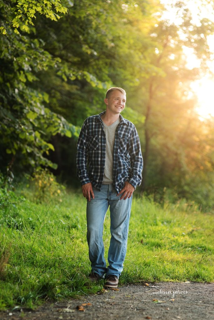 senior boy in plaid stands at sunset senior portraits in Bethel Park PA