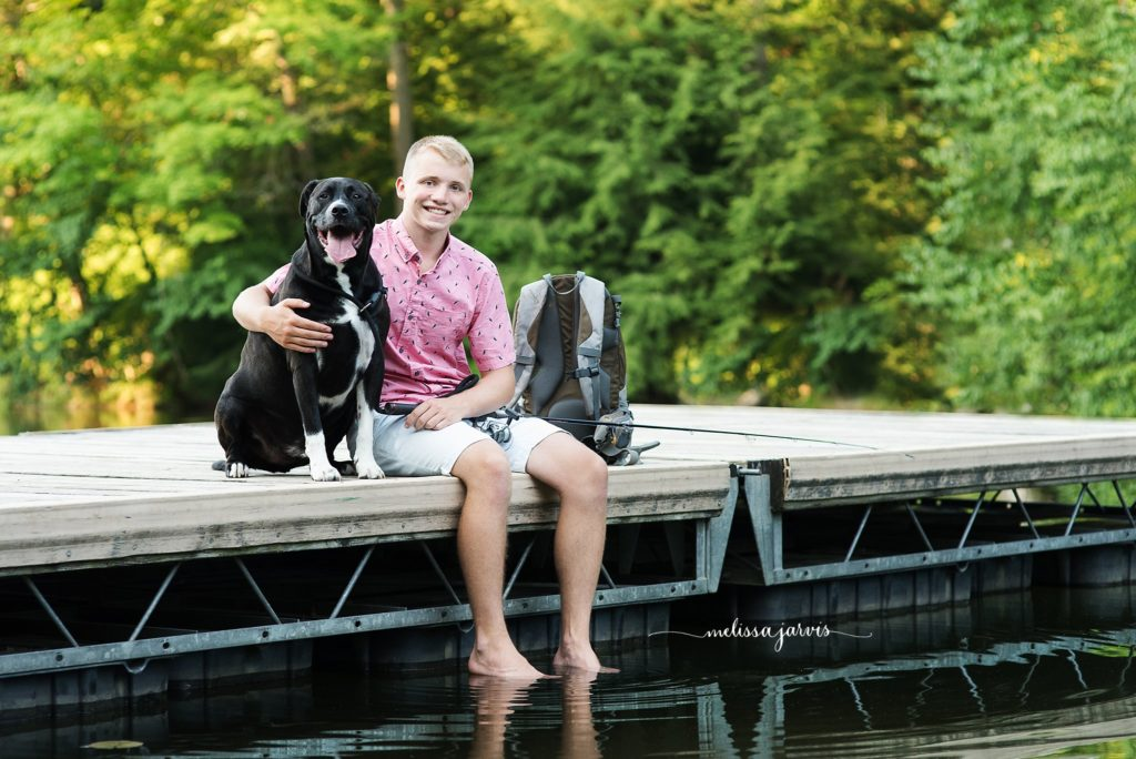 senior boy sits with his dog on a dock for senior portraits in Bethel Park PA