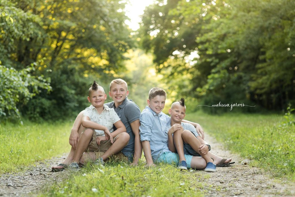 four boy siblings sit in the green grass for family portraits